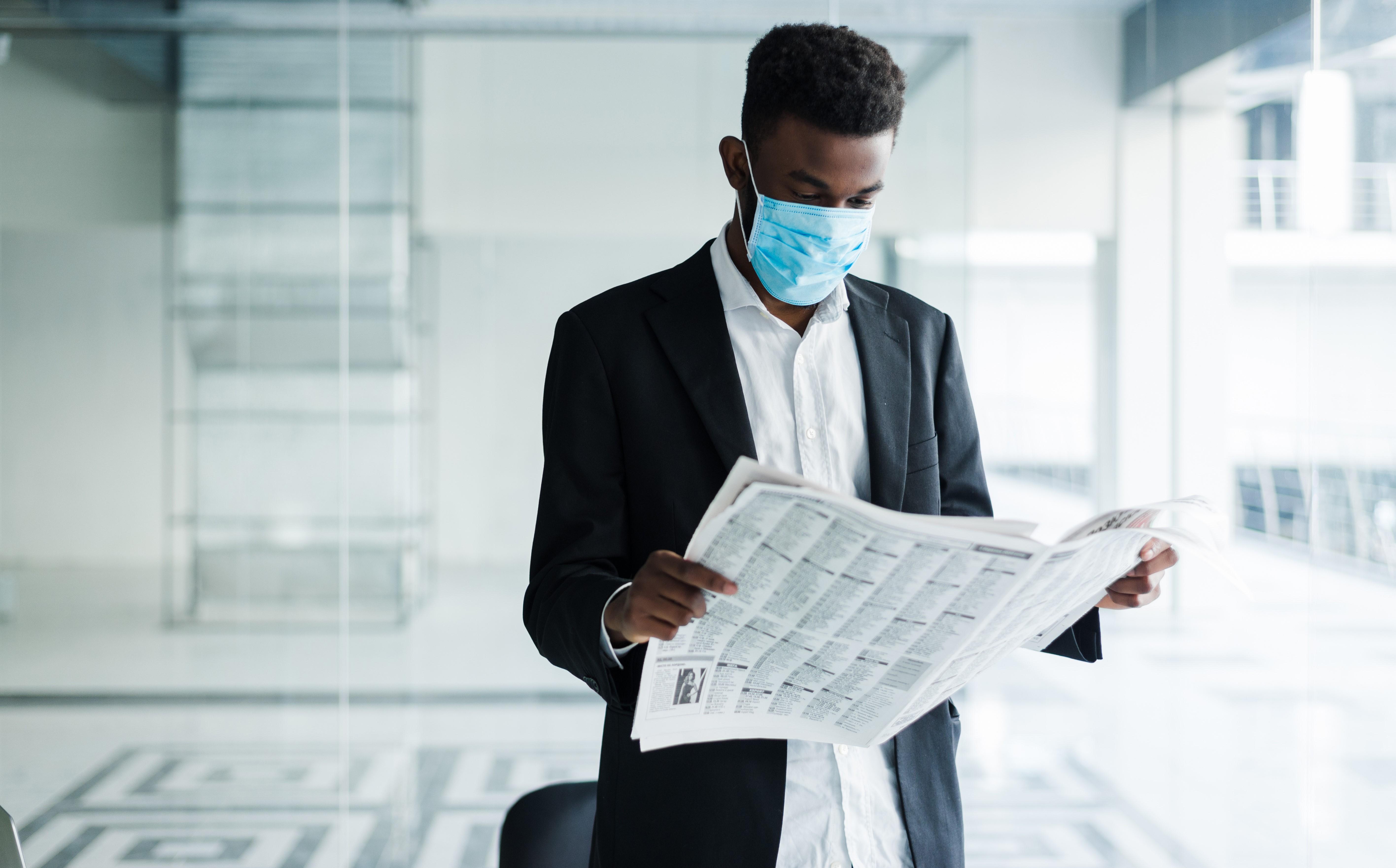 african-handsome-business-man-medical-mask-reading-newspaper-office-building-1-1